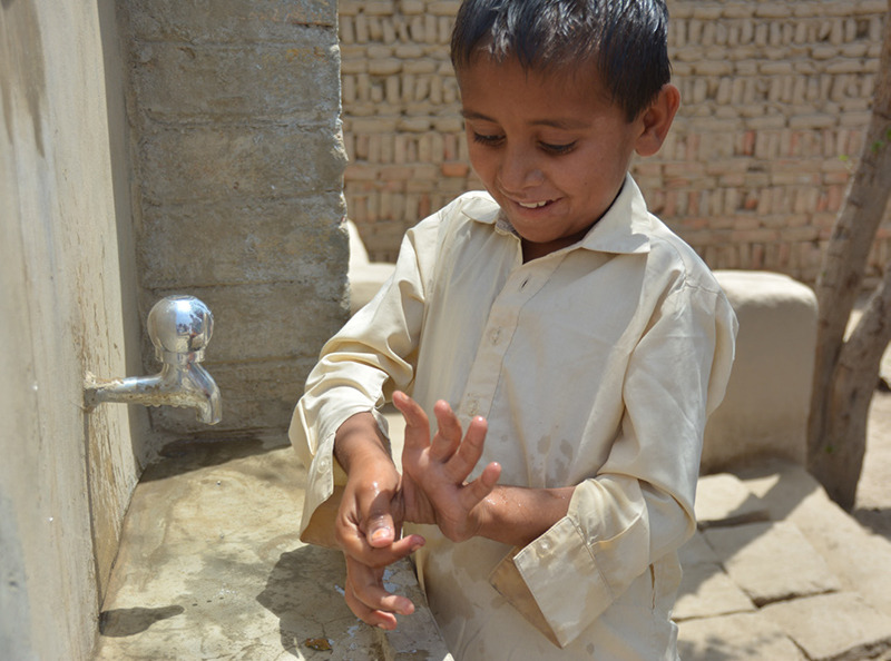 A young boy is demonstrating right method of hand-washing in Naushero Feroze, Pakistan. Photo: Margrethe Volden/Norwegian Church Aid