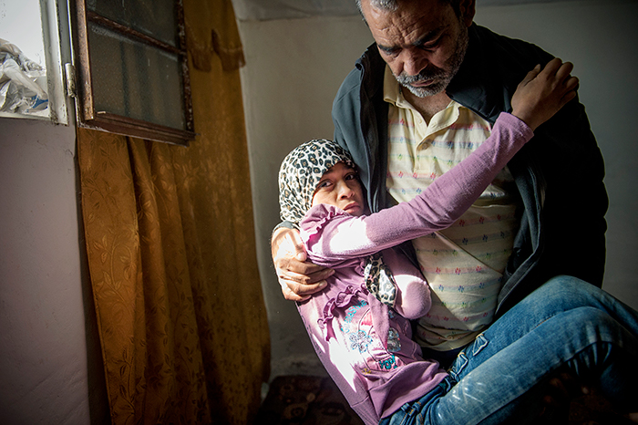 14 years old Madeline got a mental shock when she and her family got caught in a crossfire in Daraa in Syria, and became paralyzed.  Her father Mohammad is carrying her around. Photo: Håvard Bjelland.