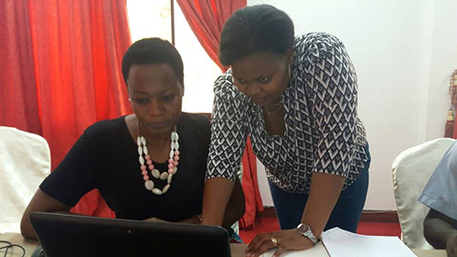 NCA's PMER, Mwajuma Davina Rwebangila assists Manka Kway, Director of Human Resources for one of NCA's core partner Tanzania Episcopal Conference.